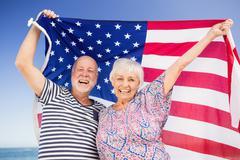 Senior couple holding american flag - stock photo
