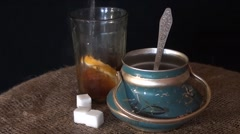 Tea is poured into the glass, the old sugar bowl and burlap on a black Stock Footage