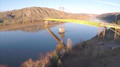 2.7K Aerial Shot Suspension Bridge Over River Trees Hills Traffic Drone Stock Footage