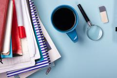 Office table desk with supplies, blank note pad, cup, pen, pc, crumpled paper - stock photo