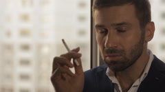 Young man smokes a cigarette at the window - stock footage