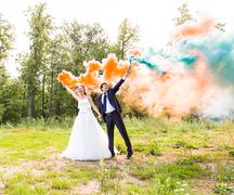 Stock Photo of Wedding couple with color smoke in the summer park