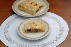 Homemade apple strudel with raisins on the plate on a wooden table, vanilla,  - stock photo