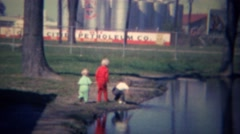 1961: Kids play in wastewater pond shore at petroleum company. Stock Footage