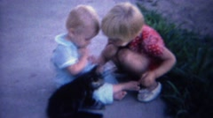 1961: Baby playing with kitten cat on sidewalk practice petting. Stock Footage