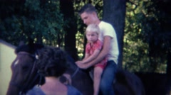 1961: Brother helps sister ride horse mom calms assures animal. Stock Footage