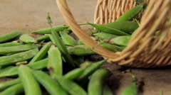 Green peas in a small wicker basket. closeup. de-focused scene. Stock Footage