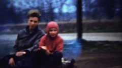 1961: Young sister driving nervous brother go kart circle muddy track. Stock Footage