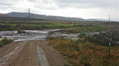 Pan-Flash flood pours over road Stock Footage