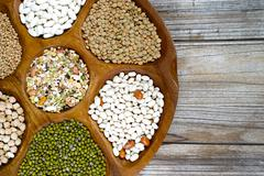 Wooden bowl of various legumes on wooden background copy space Stock Photos