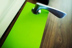 Green Door Hanger Flyer Closeup Photo. Door Hanger Marketing. - stock photo