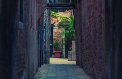 Narrow Italian Sidewalk Between Old Buildings. Venetian Architecture Theme. - stock photo