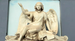 Angel Statue Against a Blue Wall in Cemetery Stock Footage
