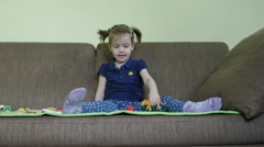 Beautiful little girl are playing with toys on the bed, dolly shot. Stock Footage