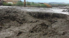 Close up-Raging flood under cuts road Stock Footage