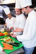 Head chef teaching his colleagues how to slice vegetables Stock Photos