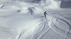 Slow motion - Aerial shot of snowboarder riding in powder snow and joining other - stock footage