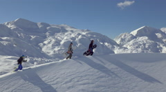 Aerial - Snowboarders and a skier walking uphill - stock footage