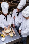 Head chef teaching his team to prepare a dough Stock Photos