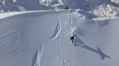 Aerial - Snowboarder goes down the slope and falls Stock Footage