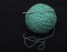 turquoise ball of acrylic-wool yarn and crochet hook on a dark background - stock photo