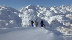 Aerial - Tracking shot of snowboarders and a skier discussing on mountain peak - stock footage
