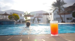 Girl resting in the pool with a cocktail Stock Footage