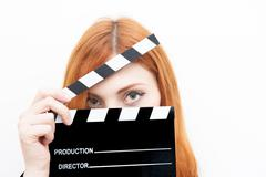Young redhead woman with clapper board - stock photo