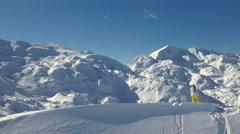 Aerial - Female hiker in winter clothing standing on mountain ridge peak Stock Footage