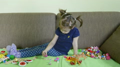 Hyperactive little girl playing on the sofa with toys, dolly shot. Stock Footage