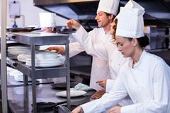 Team of chefs arranging plates on the order station - stock photo