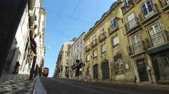 Historic 100 years old yellow tram old street in Lisbon steady cam gimbal Stock Footage