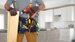 Builder handyman with drill and wooden plank. - stock photo