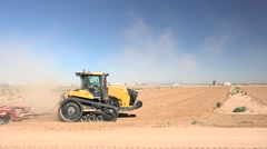 Yellow agricultural tractor plowing, cultivating Stock Footage