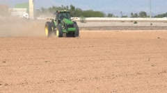 Green agricultural tractor plowing, cultivating Stock Footage