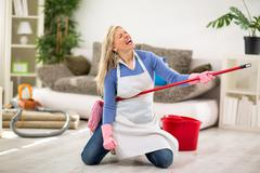 Funny female make joke while cleaning house - stock photo
