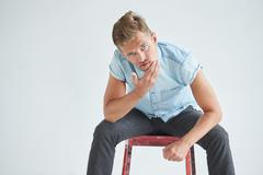 Brutal man in a shirt with short sleeves sitting in the chair , touching beard - stock photo