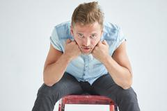 Brutal man in a shirt with short sleeves sitting on a red chair , fists - stock photo