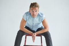 Brutal man in a shirt with short sleeves sitting on a red chair - stock photo