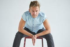 Brutal man in a shirt with short sleeves sitting on a red chair Stock Photos