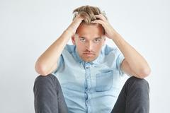 Brutal man in a shirt with short sleeves sitting on the floor, under the gaze - stock photo