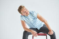 Brutal man in a shirt with short sleeves sitting on a red chair , his fists c - stock photo