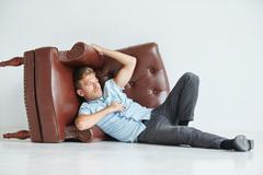 Brutal man lying next to a brown leather armchair , armchair lying on its sid - stock photo