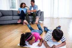 Bother and sister lying on floor and studying Stock Photos