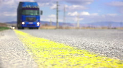 Low angle on a truck passing camera along highway line, 4k dof shot Stock Footage