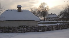 Small Rustic Houses With Wattle Fence Around Them at Wintry Landscape of a - stock footage