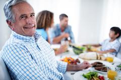 Portrait of senior man sitting at dinning table - stock photo