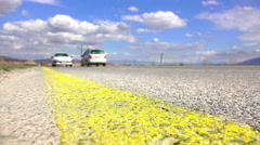 Low angle shot of traffic passing by with asphalt yellow line in focus. Stock Footage