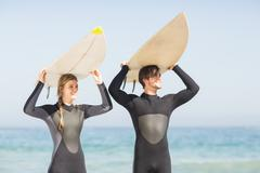 Happy couple in wetsuit carrying surfboard over head - stock photo