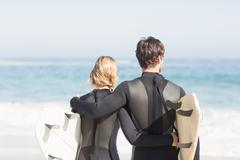 Rear view of couple in wetsuit with surfboard standing on the beach - stock photo